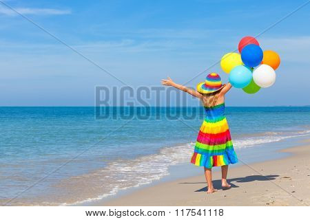 Little Girl With Balloons Standing On The Beach