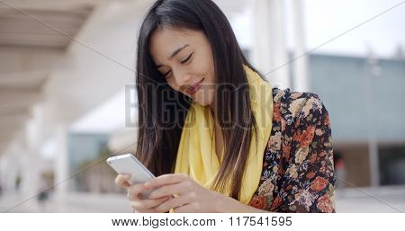Chic young woman checking her text messages