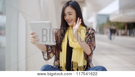 Smiling woman waving at her tablet computer