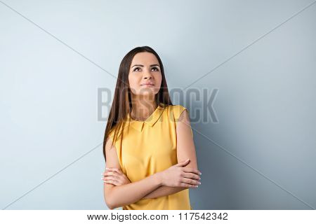 Photo of beautiful young business woman standing near gray background. Woman with yellow shirt looking up