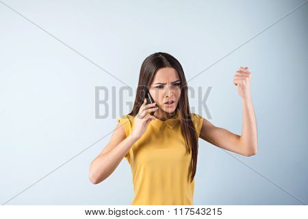 Photo of beautiful young business woman standing near gray background. Angry woman with yellow shirt screaming while using mobile phone