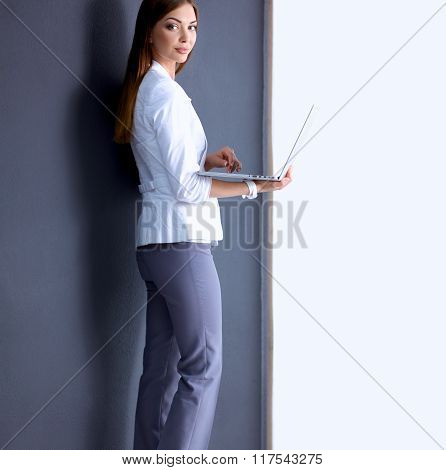Young woman holding a laptop, standing on gray background