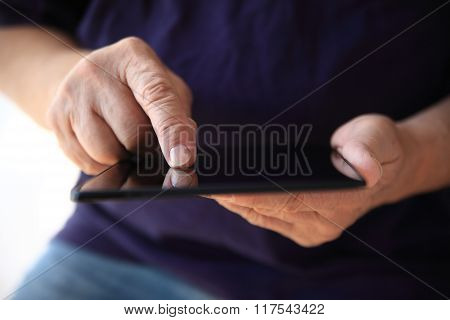 Older man uses his tablet