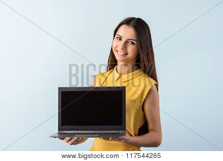 Photo of beautiful young business woman standing near gray background. Smiling woman with yellow shirt showing laptop and looking at camera