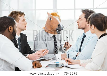 Funny photo of businessman wearing horse head and his colleagues. Businessmen and business woman working in office with big window. They using tablet computer while meeting