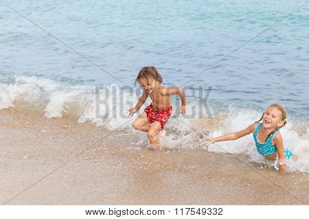 Two Happy Children  Playing On The Beach