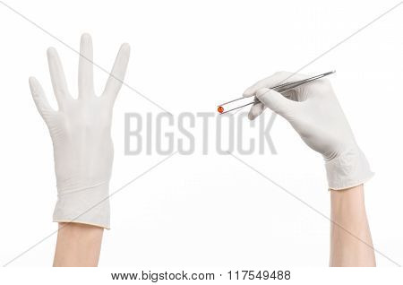 Pharmacology And Medical Theme: Doctor's Hand In A White Glove Holding Tweezers With Red Pill Capsul