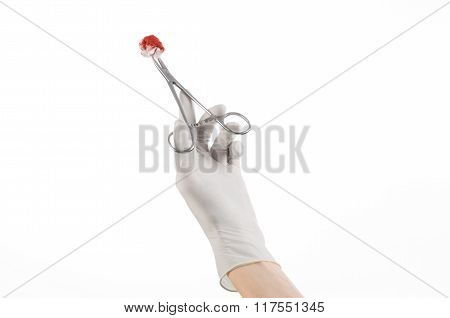 Surgery And Medical Theme: Doctor's Hand In A White Glove Holding A Surgical Clip With A Bloody Tamp