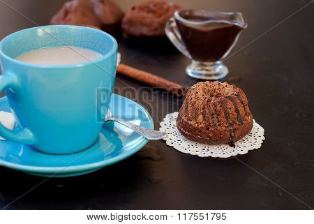 Chocolate Cupcakes Sprinkled With Cocoa And A Cup Of Coffee With Milk
