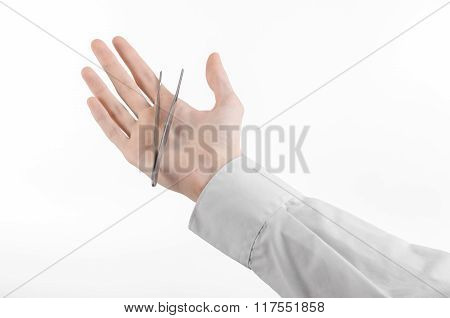 Surgical And Medical Theme: A Doctor's Hand Holding Tweezers Isolated On White Background In Studio