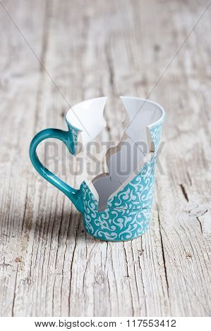 Broken Cup And Stuck Back On Wooden Table