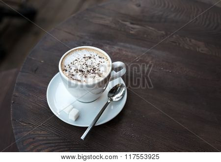 Cup of cappuccino on old dark wooden table