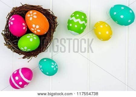 Spring nest with Easter Eggs against white wood