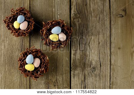 Chocolate nests with candy eggs on rustic wood