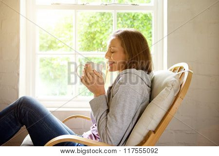 Smiling Woman Keeping Warm With Cup Of Tea