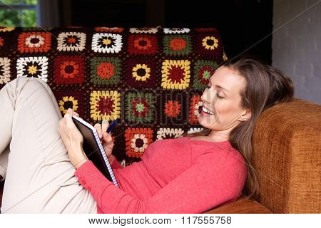 Woman Smiling And Writing In Book