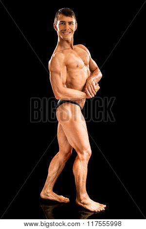 Bodybuilder posing. Studio shot on black.