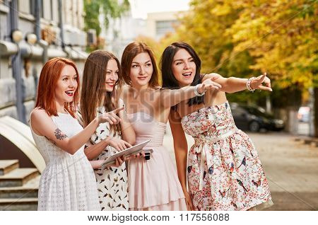 four girls toursits with tablet pc. pointing