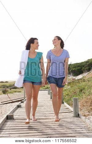 Two Female Friends Walking From The Beach