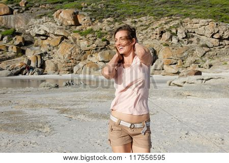 Attractive Woman Walking On Beach With Hand In Hair