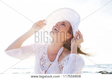 Older Woman Laughing With Hat At The Beach