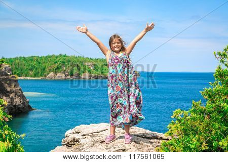 joyful little girl standing with hands up on the edge of high cliff above gorgeous amazing Cyprus la
