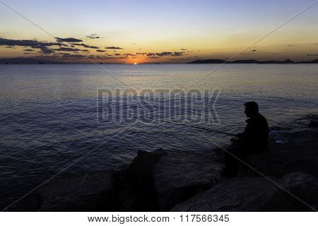 Scenic view of beautiful sunset with a fisherman silhouette