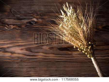 sheaf of ears on the wooden background.