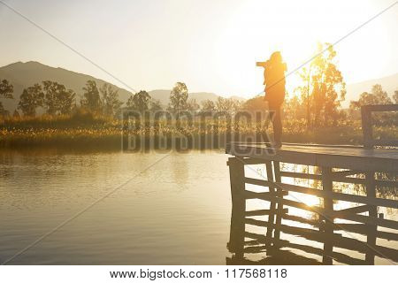Young photographer is taking photos at the sunrise on jetty , focus on the bridge