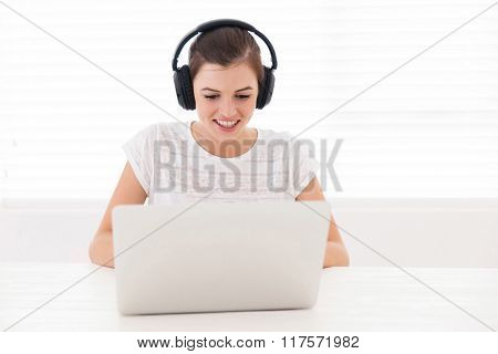 happy teen girl watching a movie on laptop