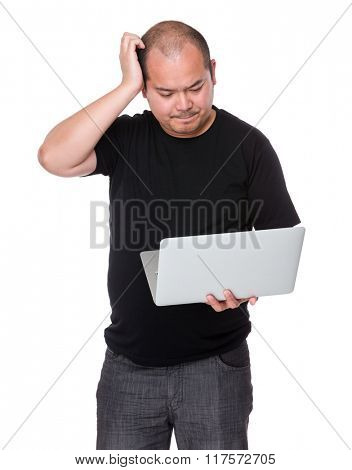 Man with laptop and scratch his head
