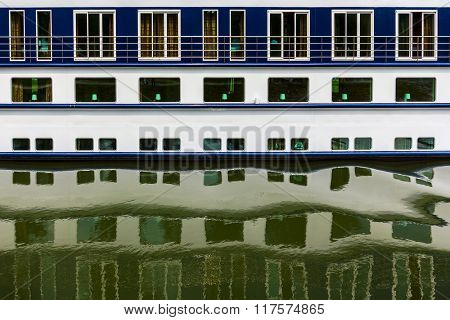 Pattern of ship windows with their reflections in water.