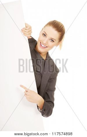 Businesswoman pointing on empty banner.