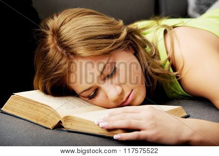 Tired woman with her head on book.
