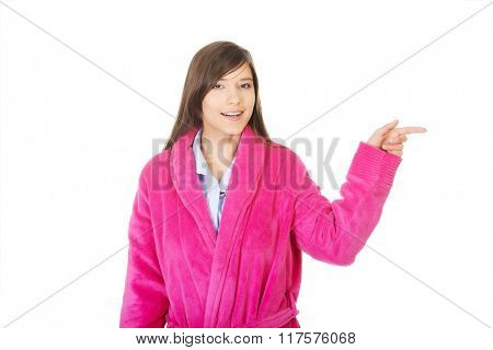 Woman in pink bathrobe pointing aside.