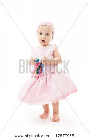 little child baby in pink dress playing with keys isolated on white studio shot