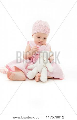 little child baby 1 year pink dress hat baby's dummy soother isolated on white studio shot playing with teddy bear