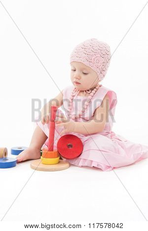 baby girl caucasian beauty pink dress playing pyramid wooden toys isolated on white studio shot