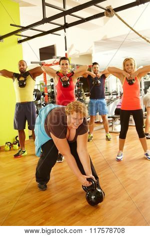 Fat woman fails to lift up dumbbell in gym, doing fitness workout in group.