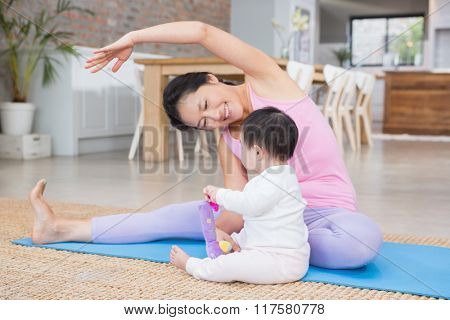 Happy mother doing yoga on mat while looking at baby daughter at home