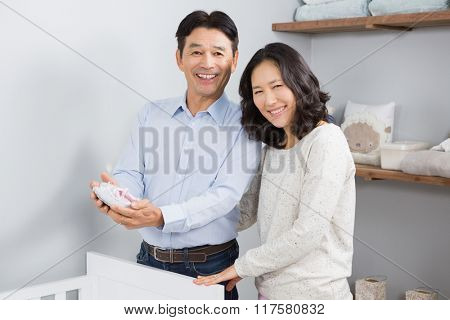 Happy couple holding baby shoes near a crib
