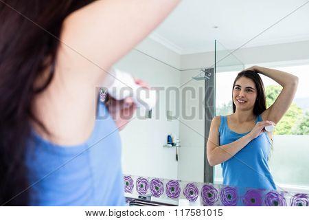 Smiling brunette putting deodorant on her armpit in bathroom