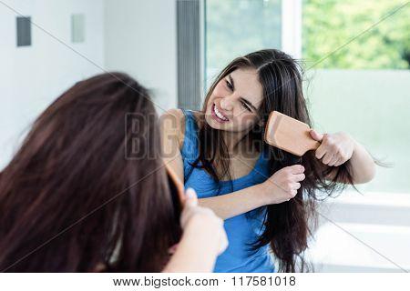 Unsmiling brunette combing in the bathroom