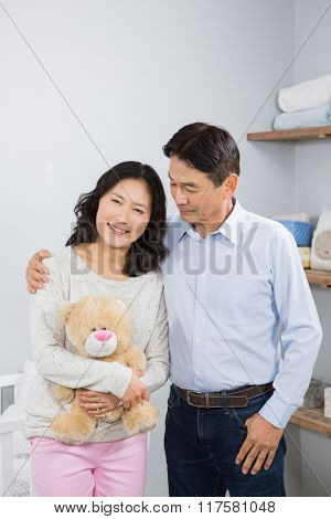 Smiling couple with teddy bear against crib