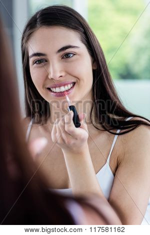 Brunette applying lip gloss in bathroom