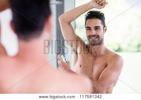 Handsome shirtless man putting deodorant in the bathroom