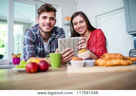 Happy couple having breakfast and using tablet at home