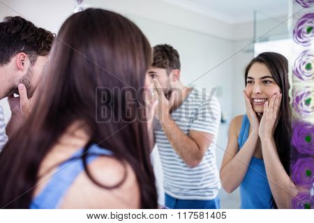 Couple looking themselves in the mirror in bathroom