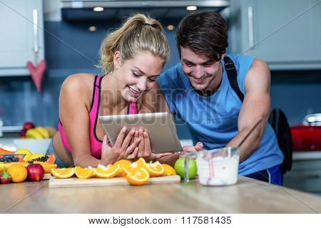 Healthy couple looking at tablet in the kitchen