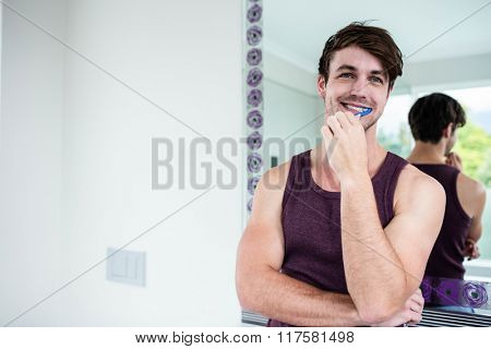 Handsome man cleaning his teeth in bathroom